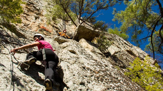 A climber working their way up the Via Ferrata rungs while safely clipped in
